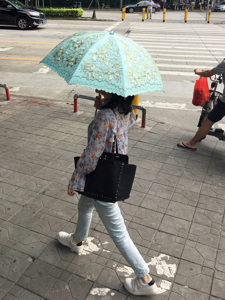 It may be 90F/31C but the women in China will wear long pants and long-sleeve shirts, and carry a parasol to keep their skin pale