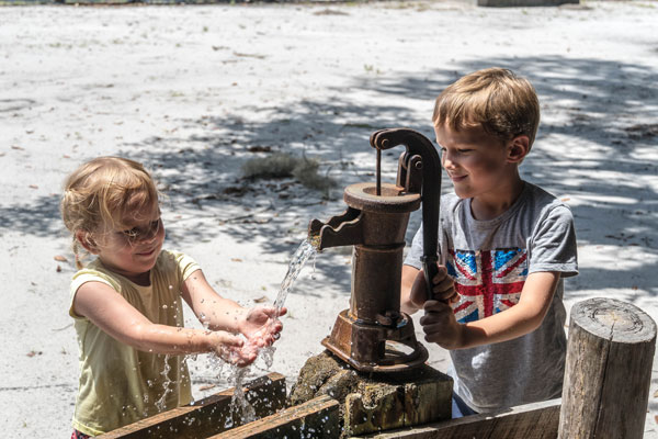 kids playing with a water pump