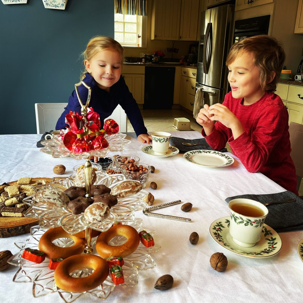 2 young kids at the table of sweets and tea