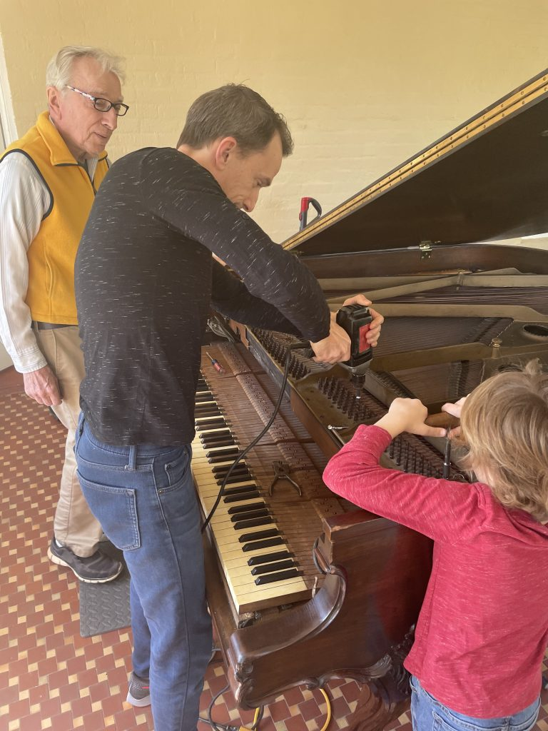 an old man, a middle-aged man, and a boy working on a grand piano